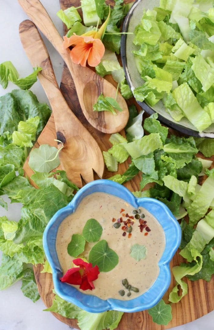 Vegan Caesar Salad Dressing Recipe with Tahini, Garlic, Lemon, Capers tossed with Romaine Leaves and Nasturtiums.