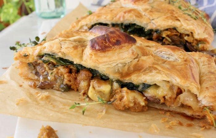 Vegan Mushroom Wellington recipe stuffed with spinach, caramelized leeks, Beyond Meat Italian sausage and plant-based smoked gouda cheese.