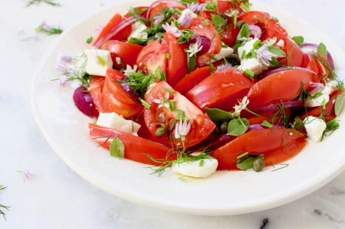 "Fresh Italian tomato salad "" insalata di pomodori "" with red onion, herbs and capers."