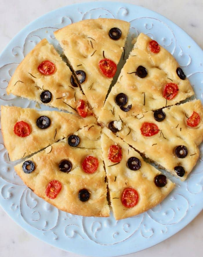 Skillet focaccia bread with rosemary, cherry tomatoes and black olives.