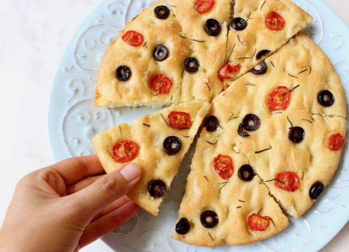 Vegan rosemary focaccia bread with black olives and cherry tomatoes.