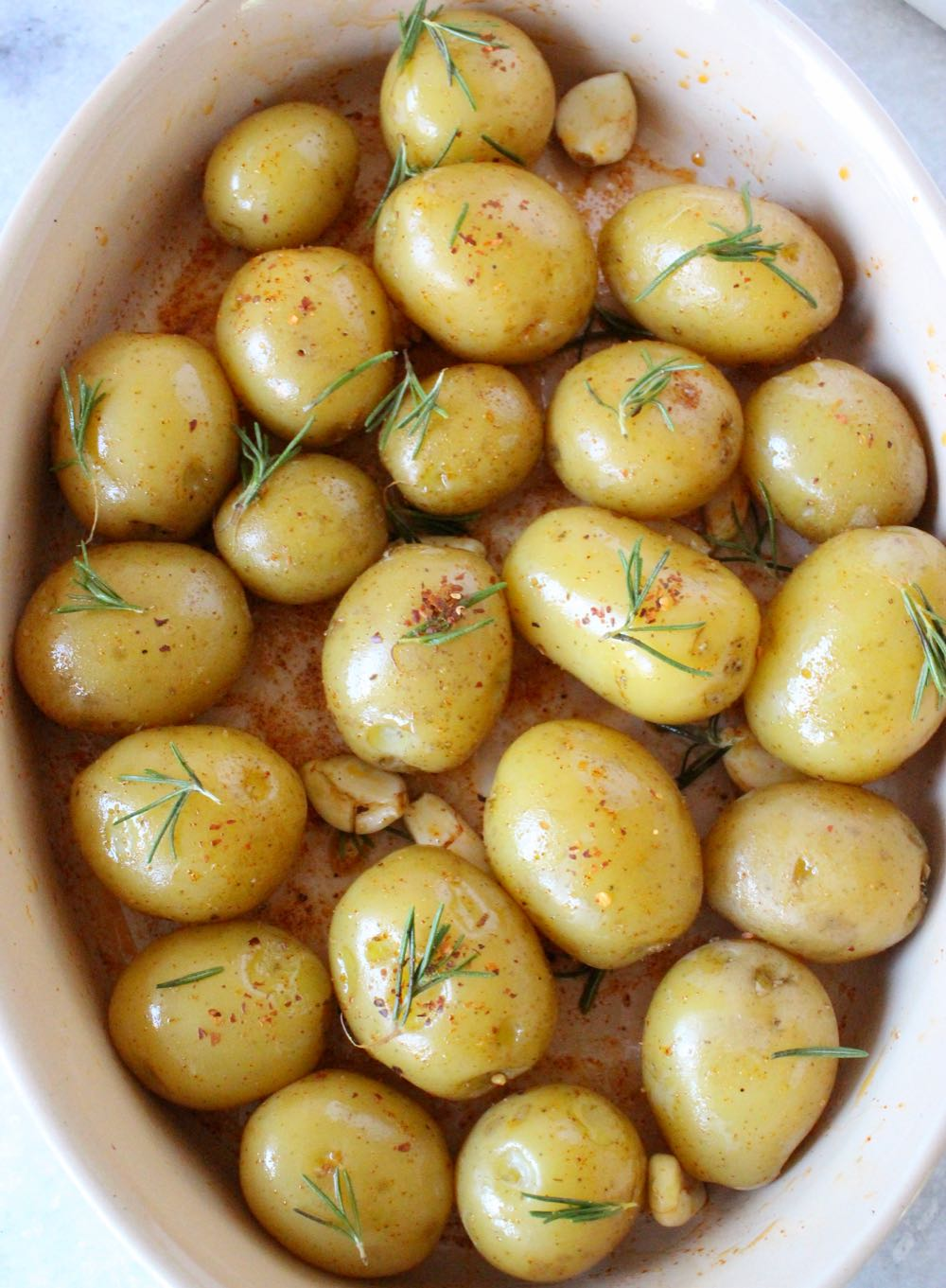 Seasoned whole potatoes for roasting with garlic and rosemary.