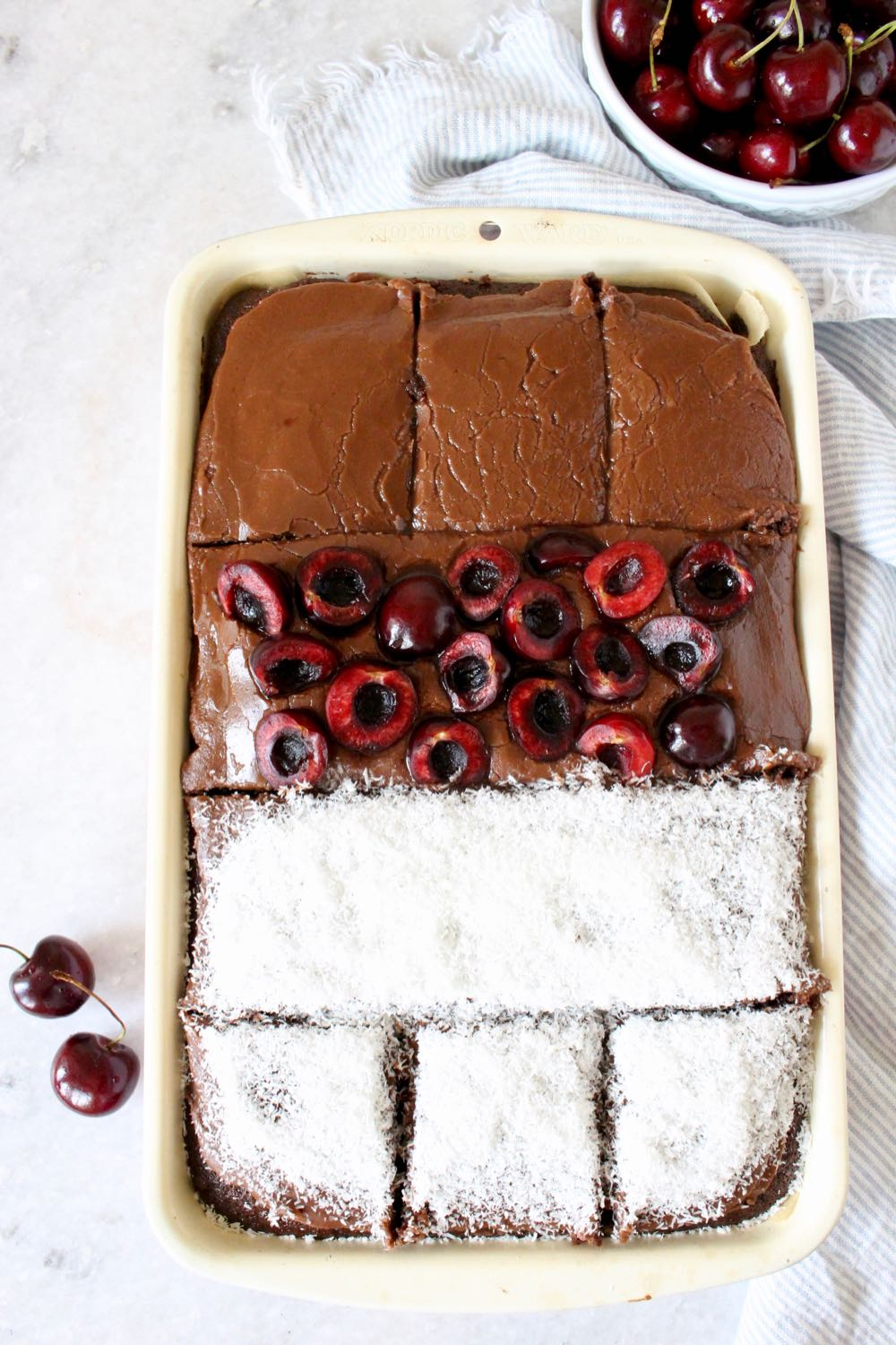 chocolate sheet cake in pan with frosting, coconut and fresh cherries